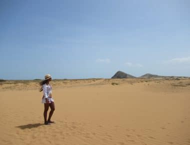 A person walking over the dunes you can see when you visit Cabo de la Vela.