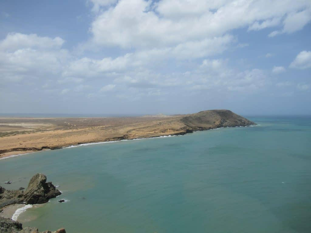 A view of a hill in the desert running into the ocean, one of the beautiful views that make up the best things to do in Cabo de la Vela.