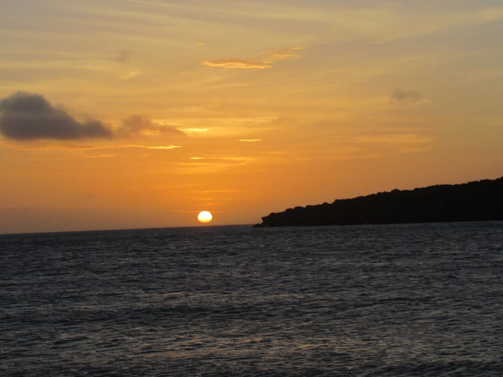 The sunset over the ocean next to a cliff from La Boquita beach, another great what to see in Punta Gallinas.