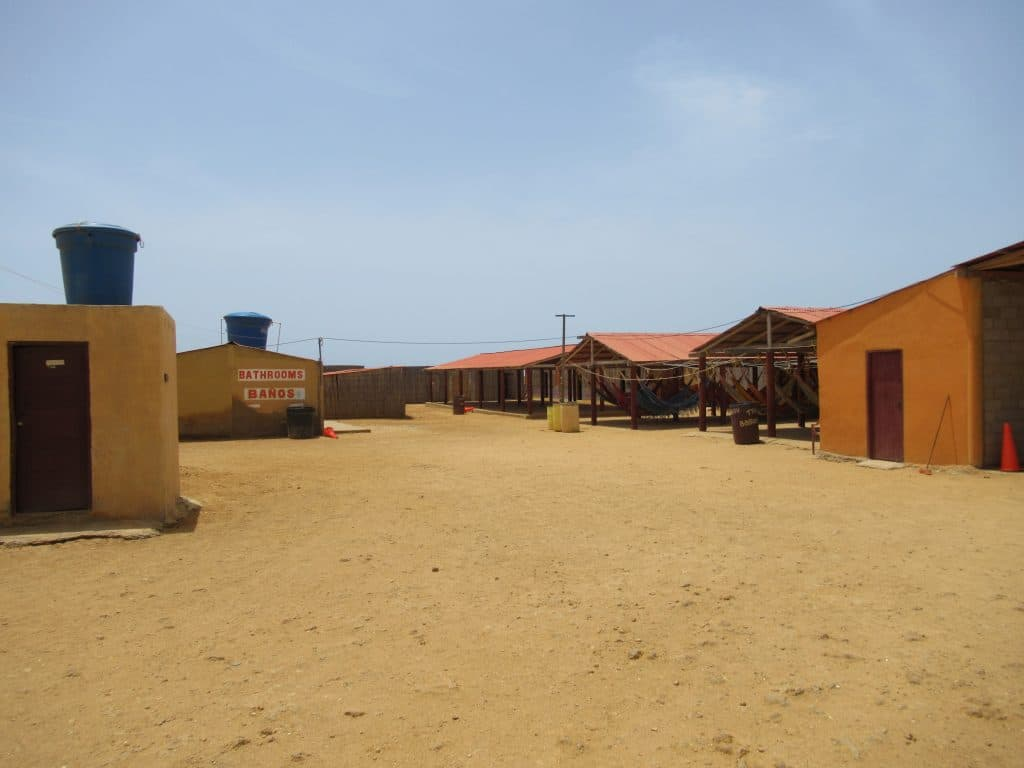 A view of the accommodations on a visit to Punta Gallinas at Hospedaje Alexandra, one of the places to stay in Punta Gallinas, showing the hammock shelters, bathrooms, and private rooms in the back.