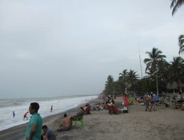 The beachfront you will see if you travel to Palomino with some people standing on the beach.