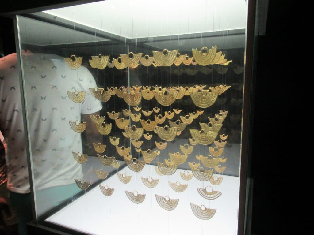 A display case full of hanging gold designs that show the weave patterns on display at the Gold Museum in Cartagena.