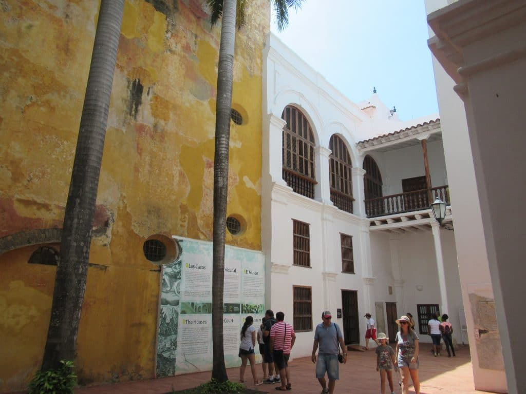 The inside courtyard with a few trees and people standing around inside the Cartagena Inquisition Museum.