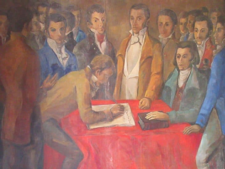 Painting of several men standing around and signing Cartagena's declaration of independence on display at the Palacio de la Inquisición.