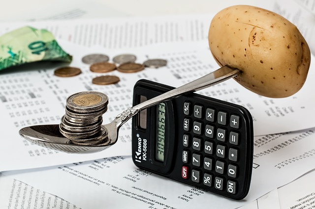A spoon on top of a calculator balancing coins and a potato.