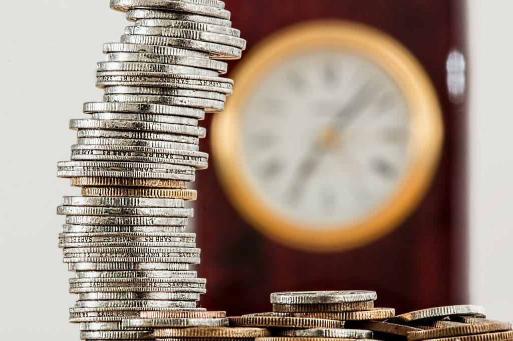 A stack of coins with a clock in the background representing how you earn cesantías over time in Colombia.