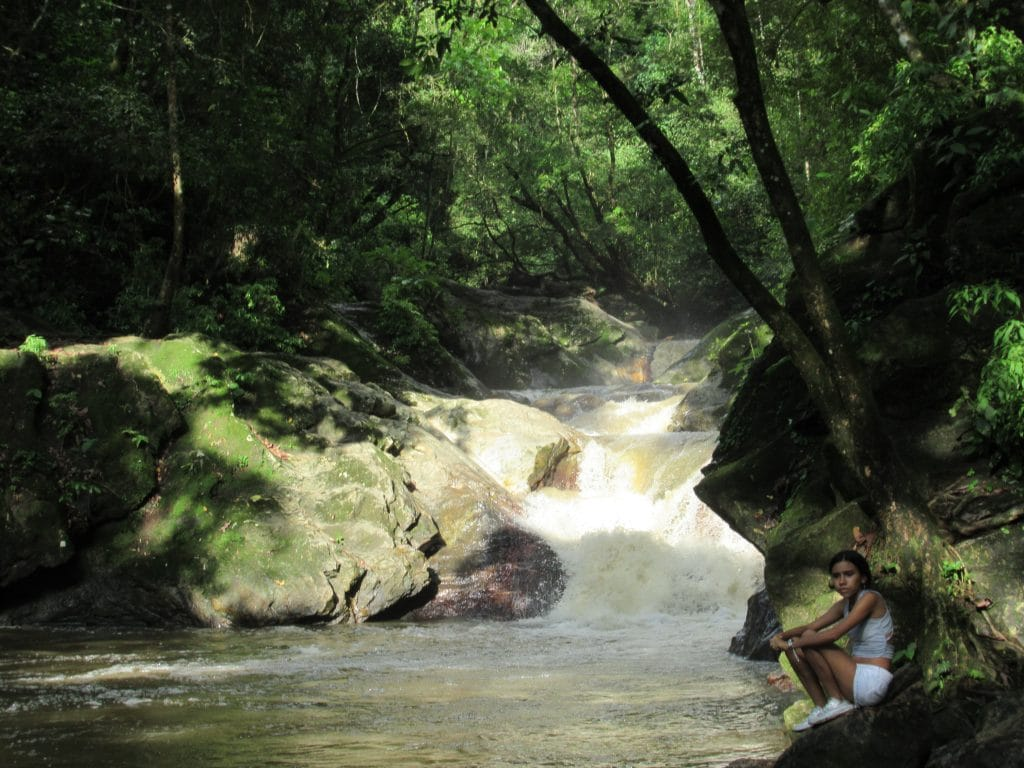 The short waterfall at Pozo Azul, one of the attractions when you visit Minca, with a girl sitting on a rock to the right.