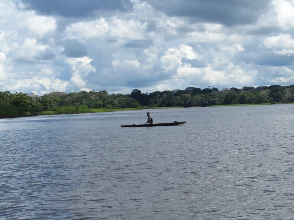 A man in a canoe on the Amazon River, one of the sights you may see if you visit Leticia.