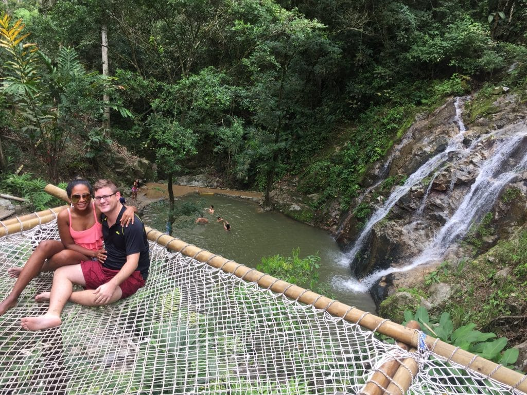 Adam and Susana sitting on a giant hammock overlooking the Marinka Waterfall, one of the best things to do when you visit Minca.