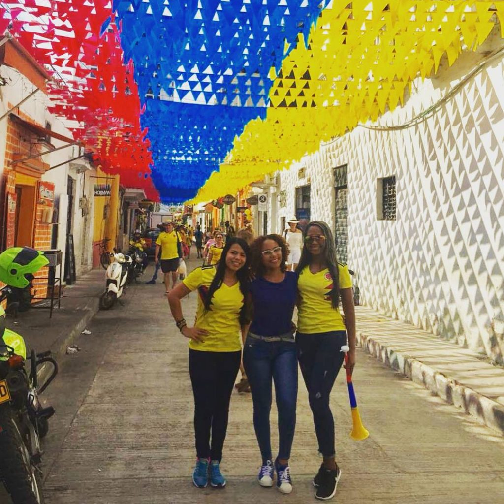 Three girls standing under little flags with the colors of the Colombian flags strung up across the street in Getsemaní, one of the best areas to stay in Cartagena.