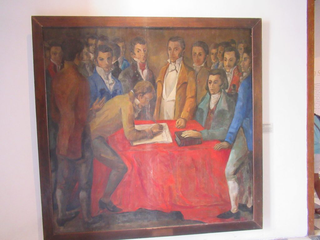A photo of a painting with some men standing around a table, signing the proclamation of Cartagena's independence.