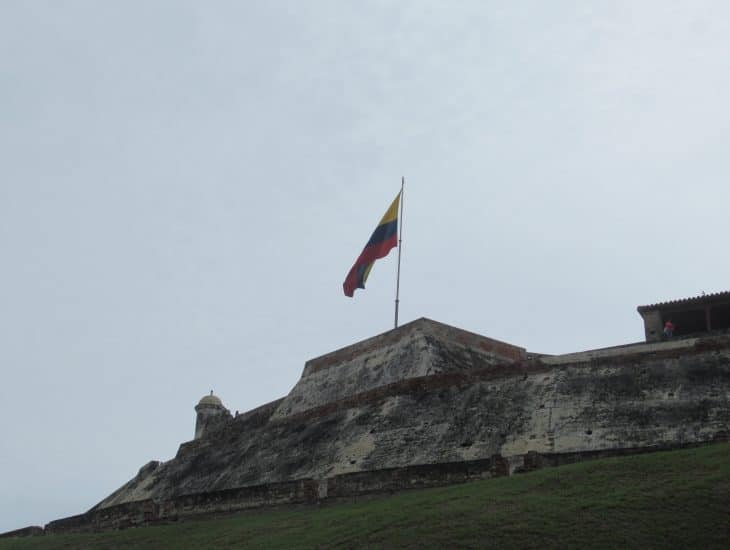 A Colombian flag flies over the walls of the Castillo San Felipe Fortress.