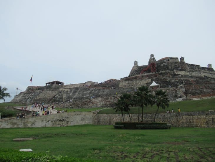 The massive San Felipe Fort in Cartagena in the background with a few palm trees in the foreground.