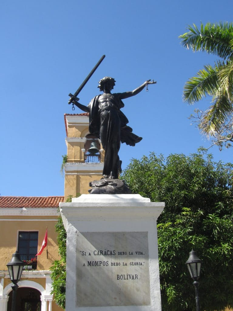 Photo of a statue holding a sword with broken chains on his wrists.