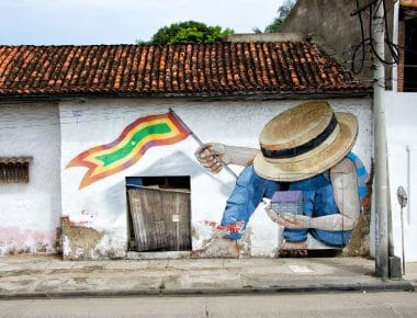 Street art showing a man holding Cartagenas flag.