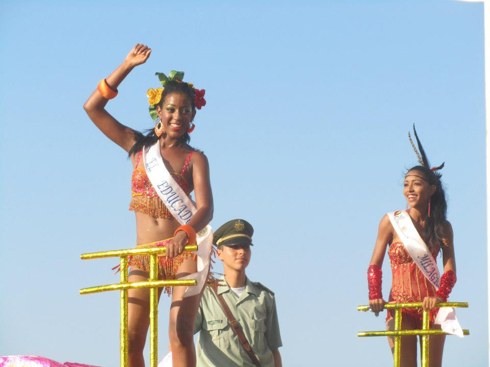 Two beauty queens dancing on a float.