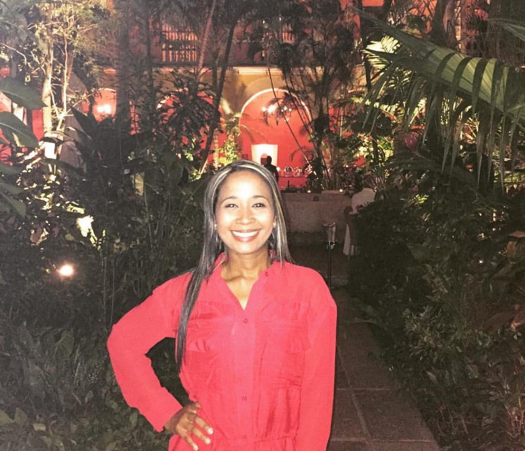 A girl posing in front of the garden at Restaurant 1621, another place on our list of where to have a romantic dinner in Cartagena.