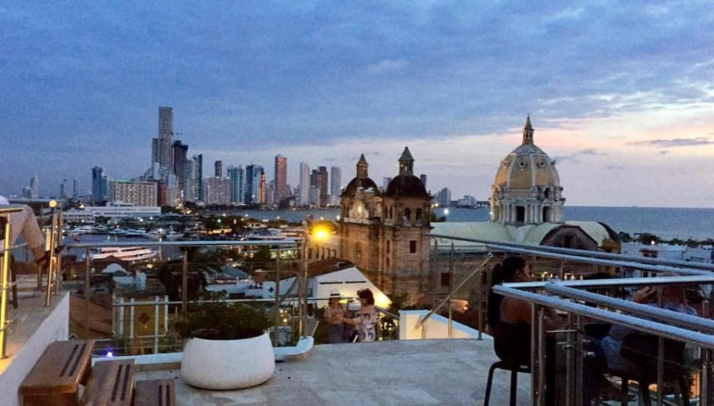Photo of the rooftop bar at Hotel Movich, a great place for where to see the sunset Cartagena, with the cathedral, bay, and skyline.