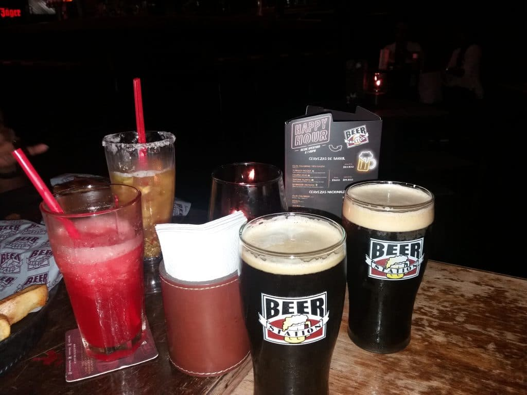 A table with two cocktails and two beers with Beer Station on the glass where craft beer is served in Cartagena.