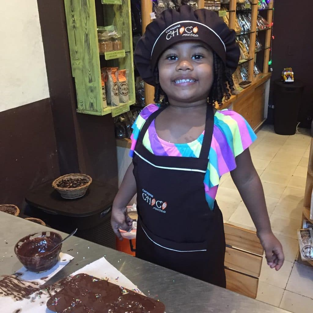 A child wearing an apron and hat smiling with her chocolate mold at the ChocoMuseo in Cartagena.