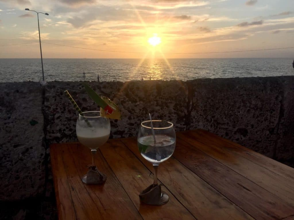 Photo of two glasses on a table with the sunset Cartagena in the background.