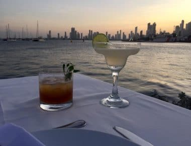 A photo of two drinks on a table with the bay of Cartagena beyond and the sky lit up with the colors of sunset taken from Club de Pesca, on our list of places to get sunset drinks in Cartagena.