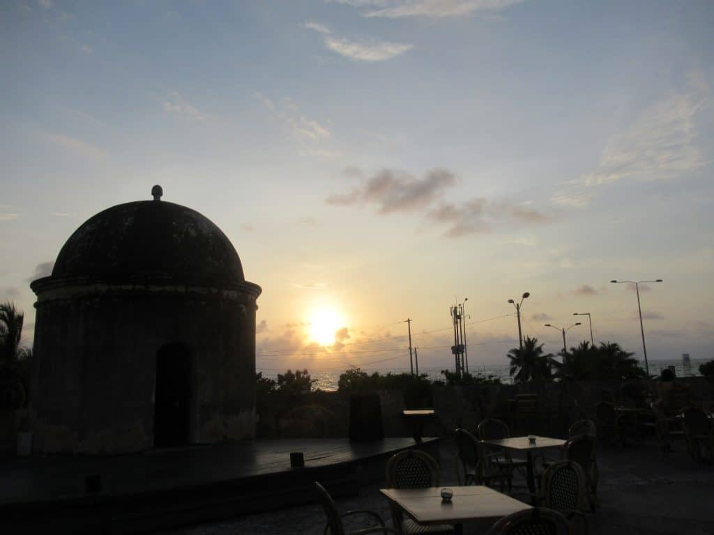Photo of the bar at Baluarte, another top pick for where to catch sunset with drinks in Cartagena, with a domed lookout tower built atop the wall and the sun setting behind some clouds over the sea.