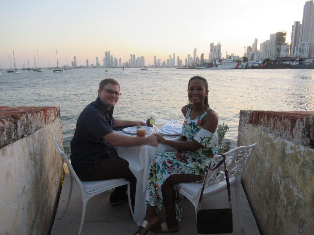 Photo of a couple at a table on the bay at Club de Pesca, one of the high end places to have a date in Cartagena.