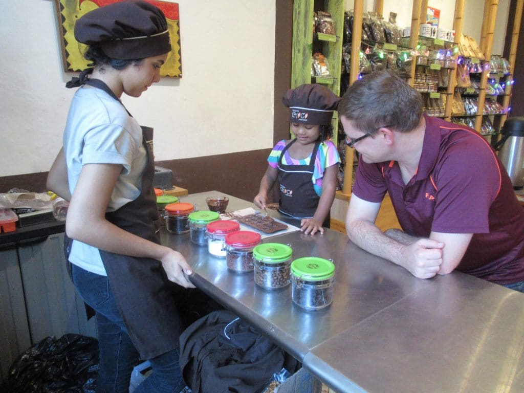 A photo of a child making her own chocolate at the ChocoMuseo, one of the places where to take children in Cartagena, Colombia.