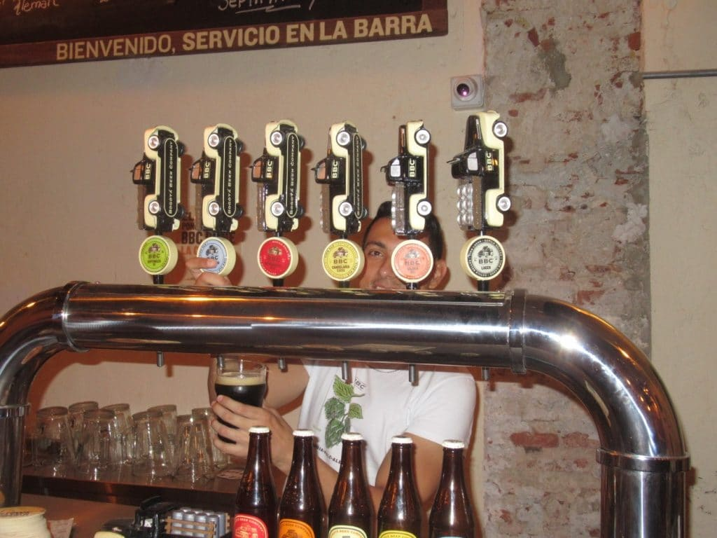 A bartender filling a glass behind a set of taps showing off the variety of BBC beers, my top pick for good craft beer in Colombia.