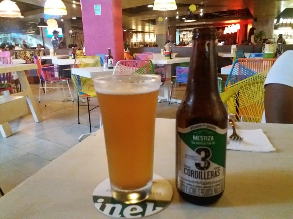 A glass of beer with the Tres Cordilleras Mestiza bottle next to it, another Colombian craft beer worth trying.