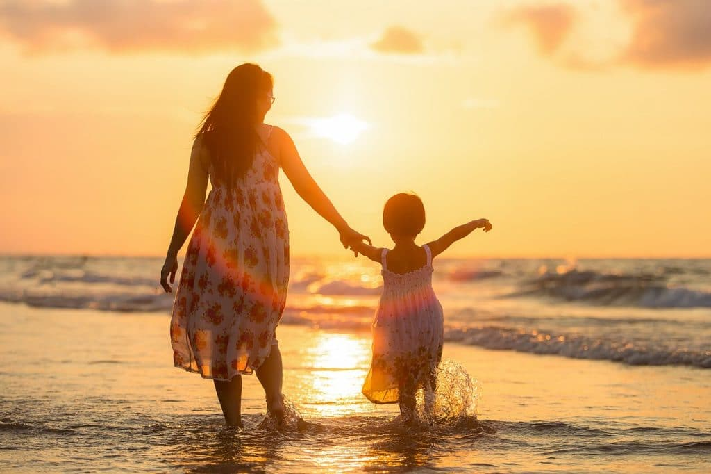 A mother and child holding hands and walking on the beach at sunset, another one of the good activities to do with children in Cartagena.