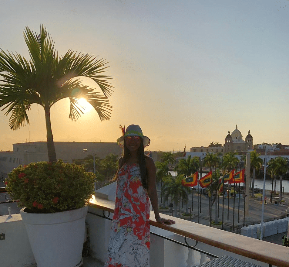 Photo of a girl standing at the corner of the terraza with a palm tree beside her and the sun setting over the city behind her taken from La Heroica Terreza another one of the places where you can get sunset drinks in Cartagena.