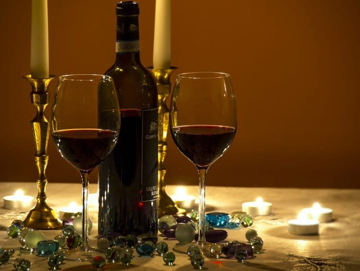 A wine bottle and two glasses sit on a table ready for a romantic dinner perhaps at one of the best places for a date in Cartagena.