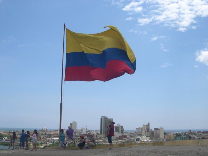A large Colombian flag flying over the Castillo San Felipe with some people standing under it, another one of the great places to take photos in Cartagena.