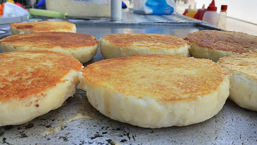 Photo of several grilled arepas on a grill, another one of the popular street food items in Cartagena.
