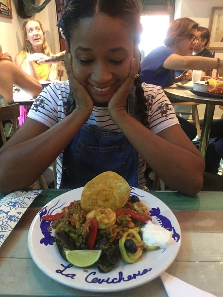 Photo of a girl looking down excitedly at a plate of seafood rice, the next thing on our list of local dishes to try in Cartagena.