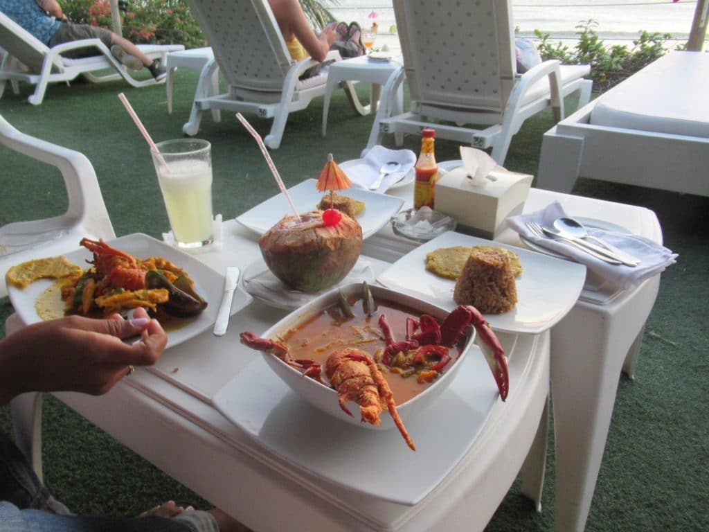 Photo of a table full of seafood with a coco loco and limonada, some of the great food and drink that are reasons why you should travel to Cartagena in 2019.