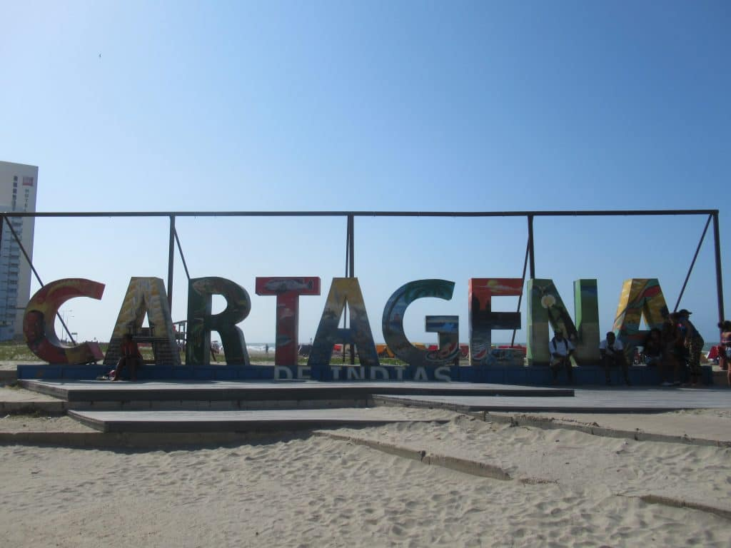 Photo of the Cartagena sign on the beach with a few people sitting on it. The sign spells out the letters of Cartagena with images representing the city on each letter.