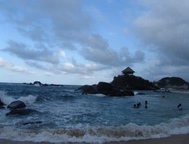 Photo of some people swimming in the water with a mound of rocks with a shelter on top at Tayrona to introduce this travel guide to Tayrona in Colombia.