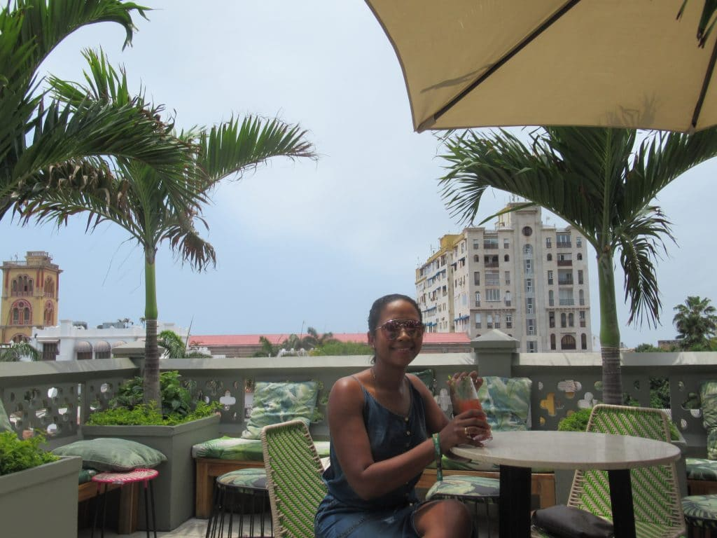 Photo of a girl with a drink with the view from Townhouses rooftop bar in the background.