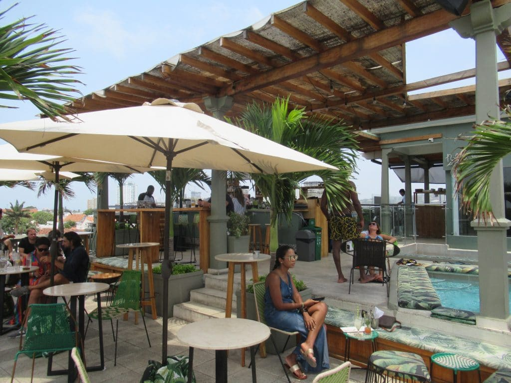 Photo of the bar at Townhouse showing some umbrellas, a girl sitting, and the corner of the small pool.
