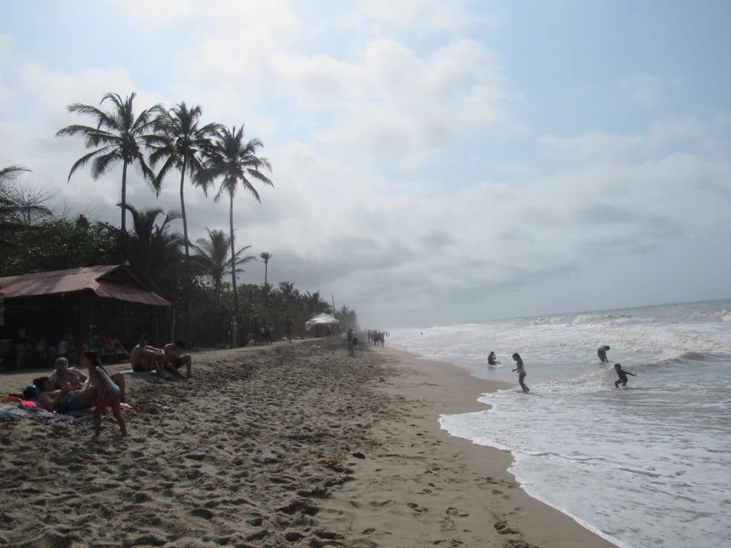 Photo of the beachfront in Palomino, Colombia, with some people wading in the water and clouds and palm trees in the background.