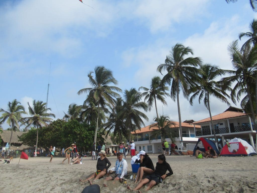 Photo of a few people sitting in the sand on the beach in Palomino, Colombia.