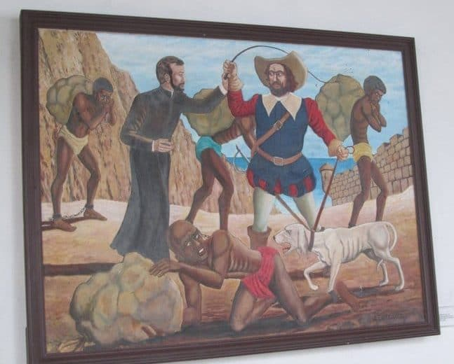 Photo of a painting showing San Pedro Claver trying to stop a man from whipping a slave.