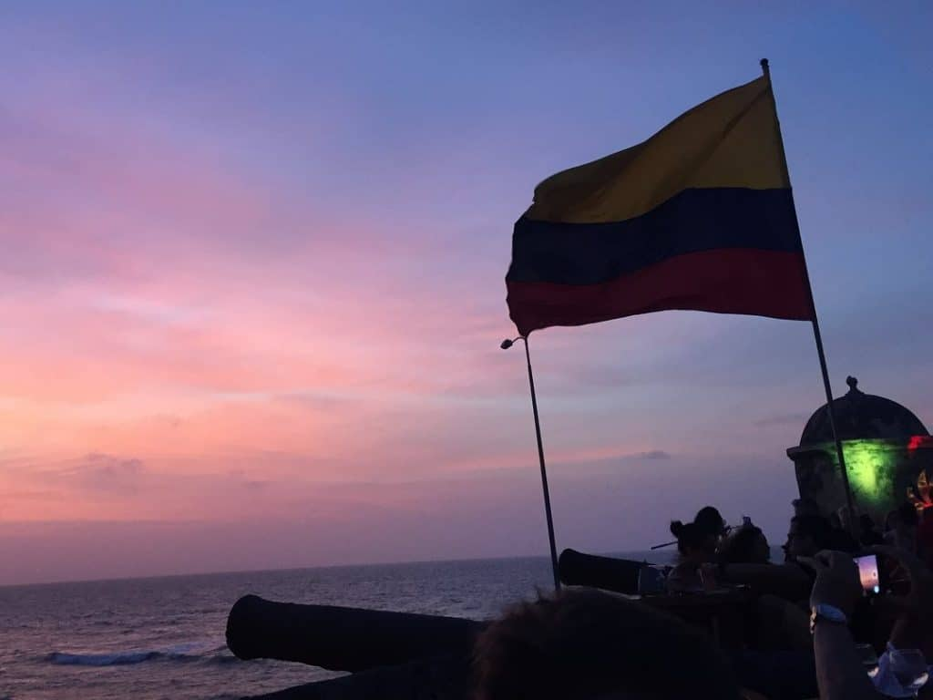 Photo of sunset from Café del Mar, another one of the must things to do in Cartagena, with a cannon and Colombian flag.
