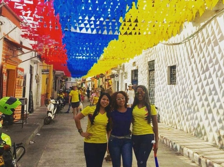 Photo of 3 girls standing under little flags the colors of the Colombian flag in Getsemaní.