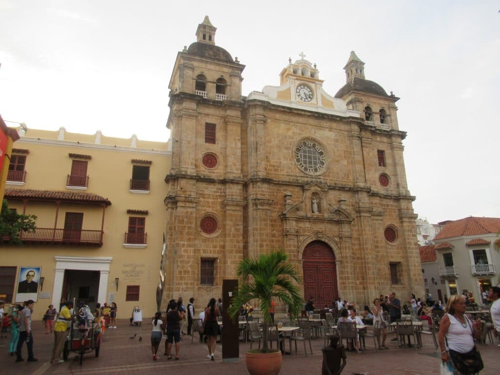 Photo of the San Pedro Claver Church in Cartagena with people standing in the plaza in front of it.