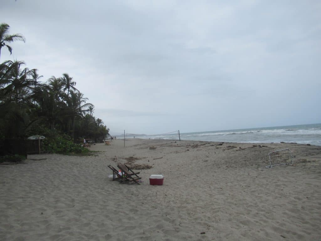 Photo of the beach at Costeño Beach with two chairs and a cooler sitting on the sand.