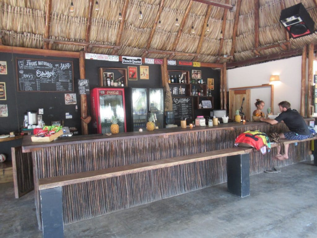 Photo of a bar front with one person sitting on a long bench at Playa Costeño.
